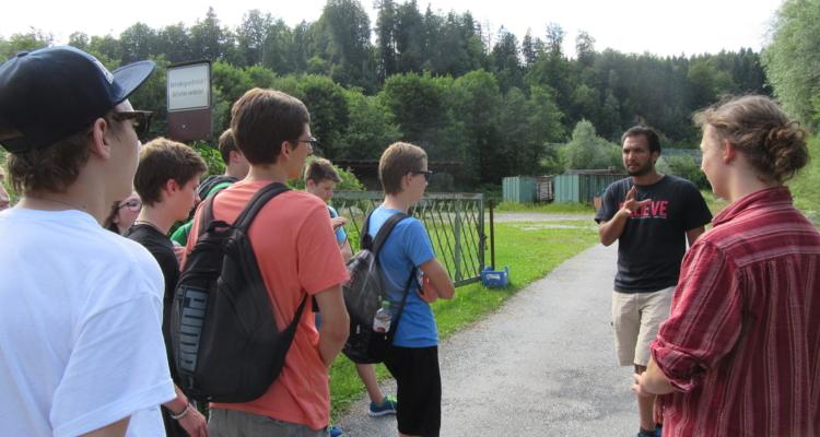 Workshopleiter Aaron Peterer, Koordinator des Anne Frank Vereins Österreich, mit den Jugendlichen beim ehemaligen Standort des Durchgangslagers in Söcking